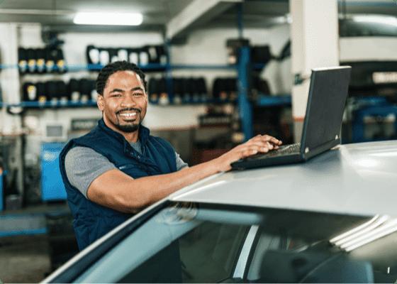 Um mecânico de automóveis a sorrir com um portátil
