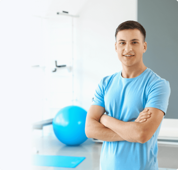 Fit man with a smile standing in a yoga room