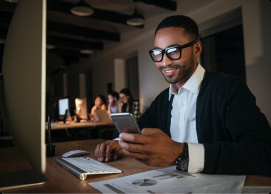Homem no espaço de trabalho a olhar para o seu telemóvel com um sorriso