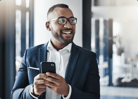 Un homme souriant tenant un mobile dans ses mains
